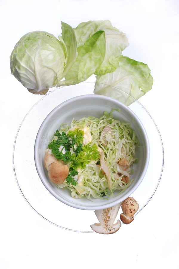 Salad with cabbage leaves and mushrooms in white bowl. close up royalty free stock photo