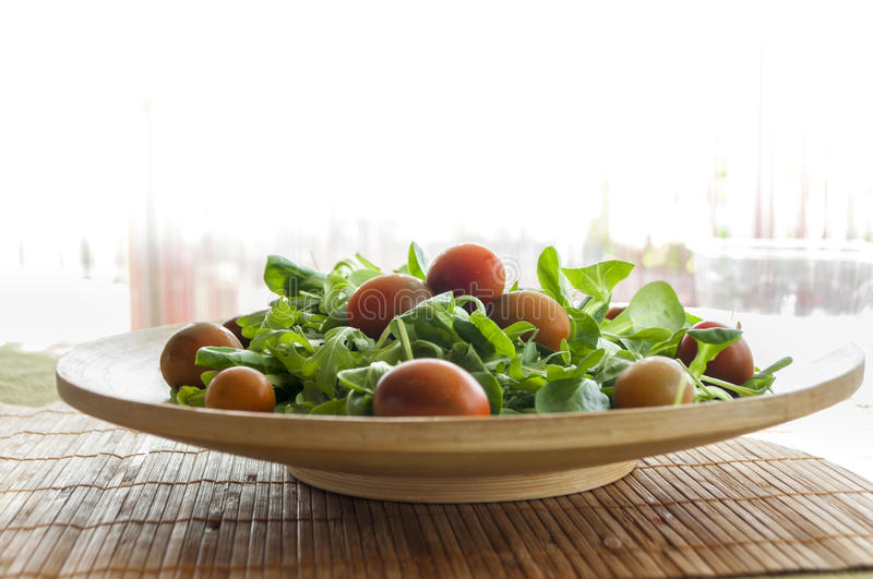Salad with cherry tomatoes. In wooden plate arugula leaves and cherry tomatoes, whole and cut stock photography