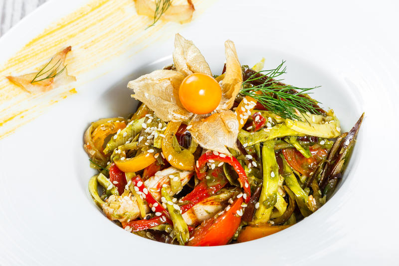 Salad with chicken breast and grilled vegetables, eggplant, sweet pepper, tomatoes, avocado and physalis on plate stock images