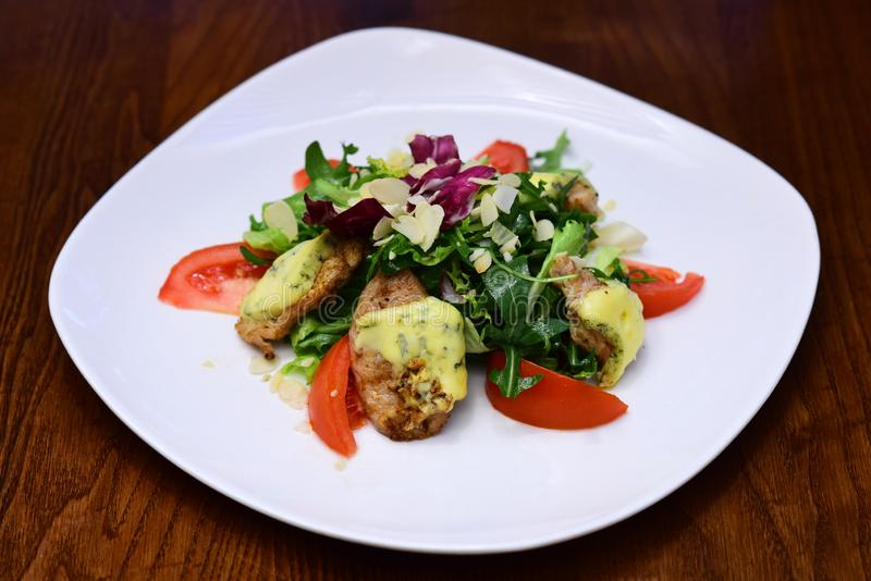 Salad with chicken breast meat and cheese. Mixed salad dish with fresh tomato and leaves of arugula and lettuce on plate stock photos