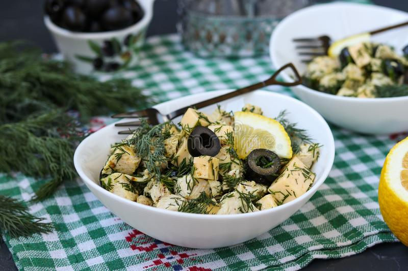 Salad with chicken, cheese and black olives in white bowls on the table. Salad with chicken, cheese, dill and black olives in white bowls on the table royalty free stock photos