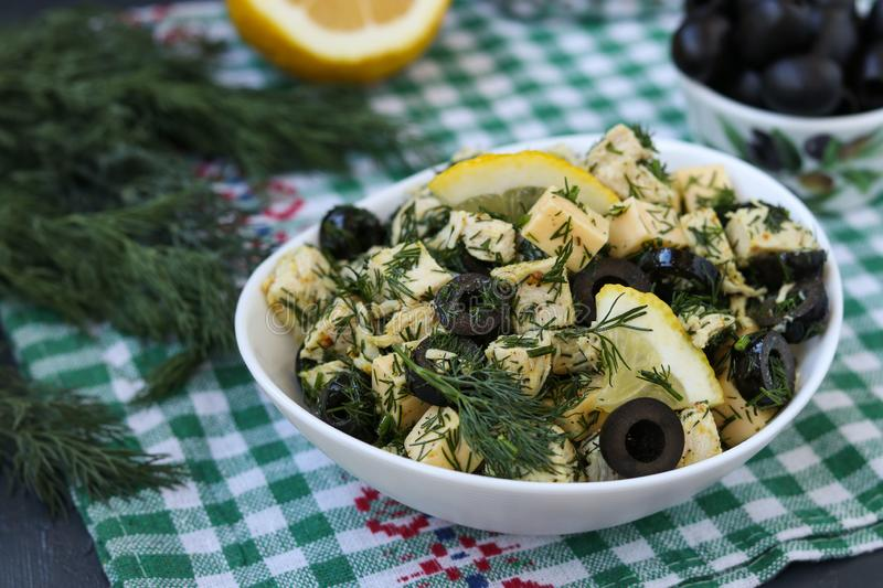 Salad with chicken, cheese and black olives in white bowls on the table. Salad with chicken, cheese, dill and black olives in white bowls on the table stock image