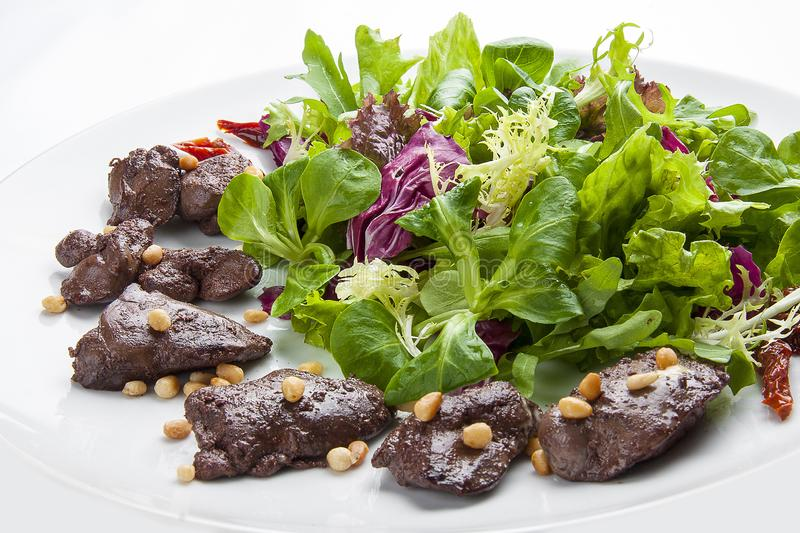 Salad with chicken liver and pine nuts on a white plate royalty free stock images