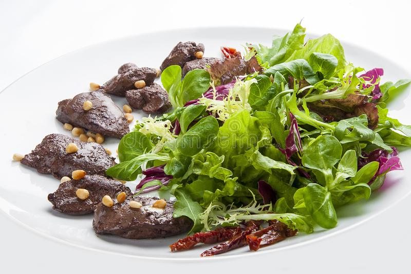 Salad with chicken liver and pine nuts on a white plate royalty free stock photography