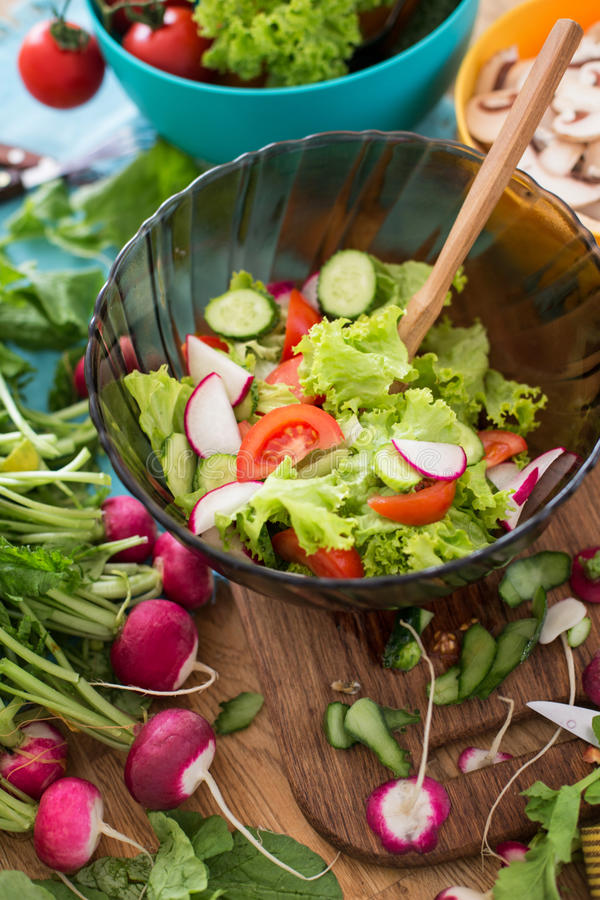 Salad from chopped spring vegetables in the glass bowl royalty free stock photo