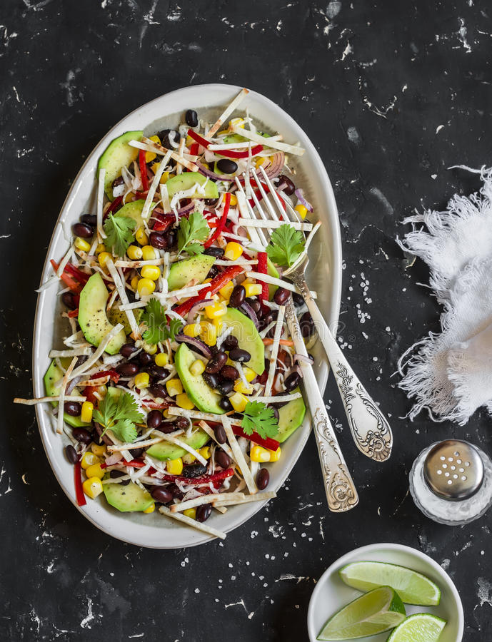 Salad with corn, beans, avocado and tortilla. Mexican black bean salad. On a dark background. Top view stock image