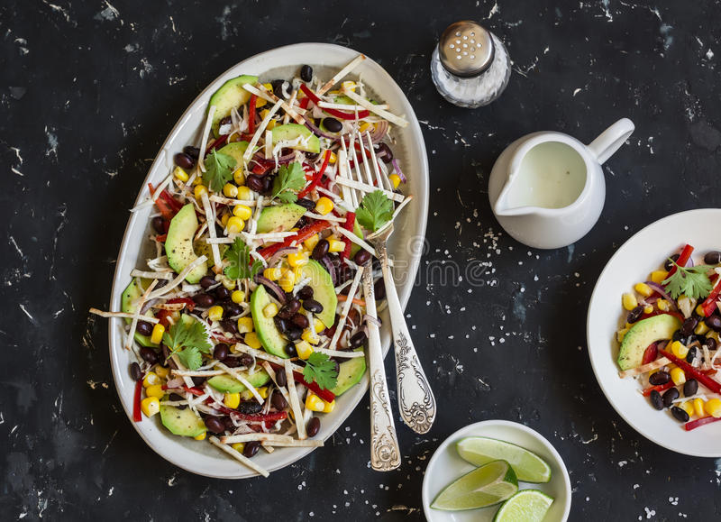 Salad with corn, beans, avocado and tortilla. Mexican black bean salad. On a dark background. Top view stock photos
