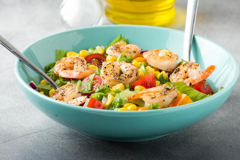 Salad with corn, fried shrimp, cherry tomatoes, red onions and lettuce. Fresh tasty lunch, healthy food royalty free stock photo
