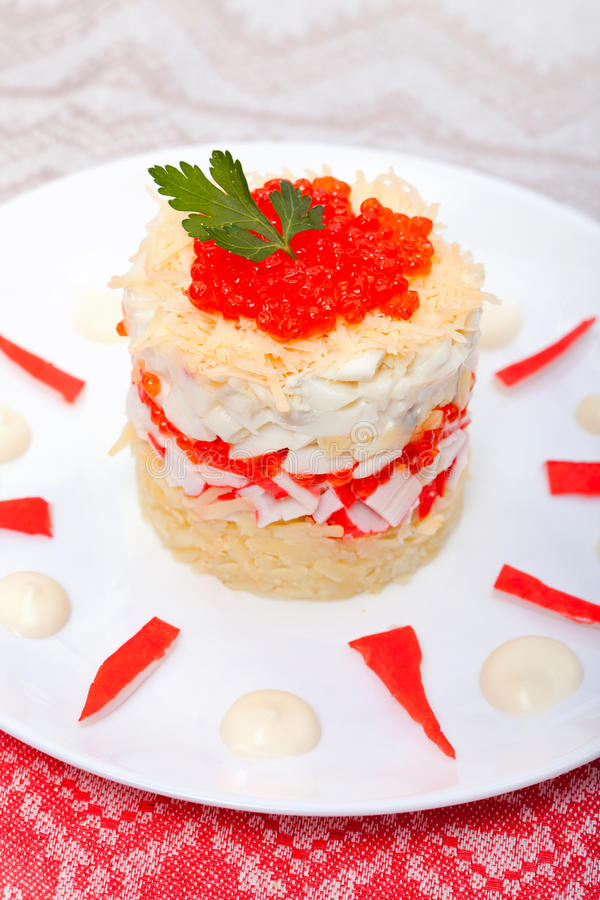 Salad of crabs with red caviar. For snack on a plate royalty free stock image