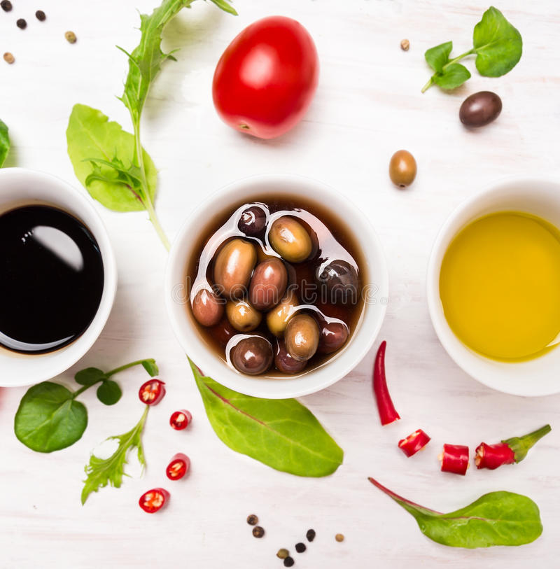 Salad dressings in white bowls with spices, olives and wild herbs royalty free stock photo