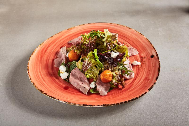 Salad with Duck Breast and Potato Balls with Greens Mix and Sauce on Ceramic Plate royalty free stock image