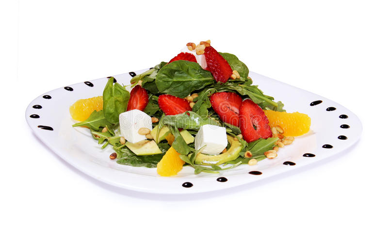 Salad with feta cheese and vegetables, arugula, strawberries royalty free stock image