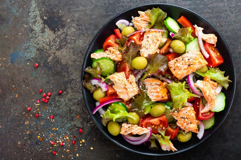 Salad with fish. Fresh vegetable salad with salmon fish fillet. Fish salad with salmon fillet and fresh vegetables stock image