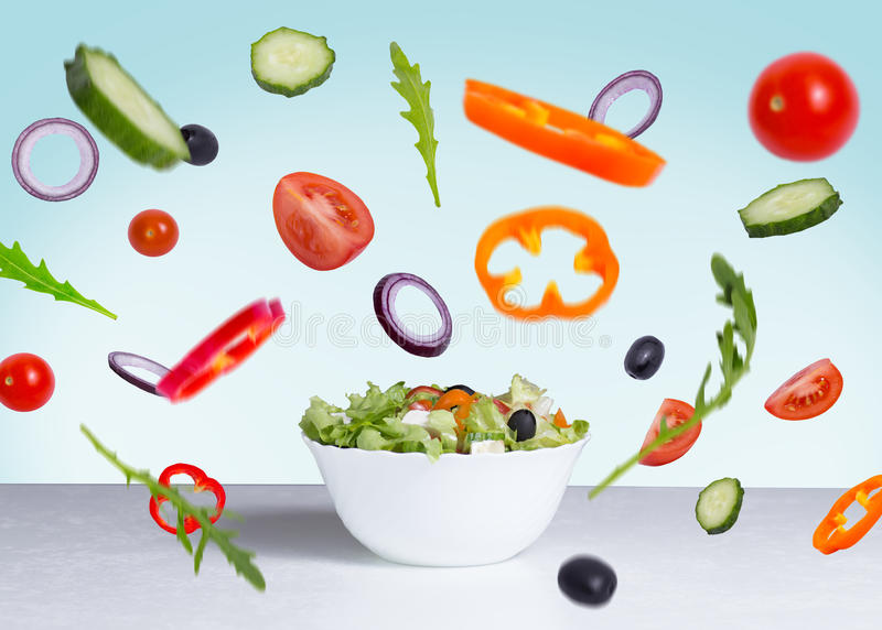 Salad with flying vegetables stock images
