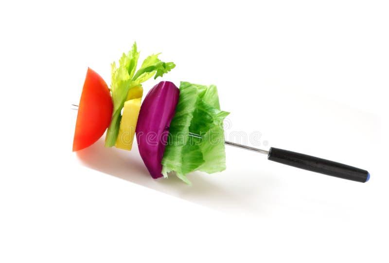 Salad on fondue fork stock photo