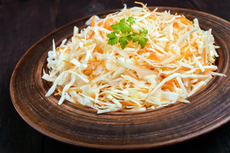 Salad of fresh cabbage and carrots in a clay bowl on dark wooden background. royalty free stock photo