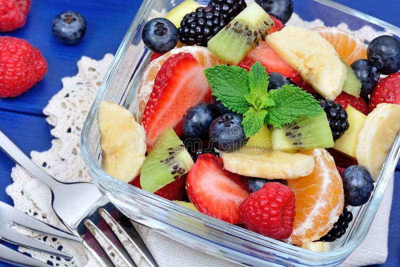 Salad with fresh fruits and berries in a transparent bowl royalty free stock photography