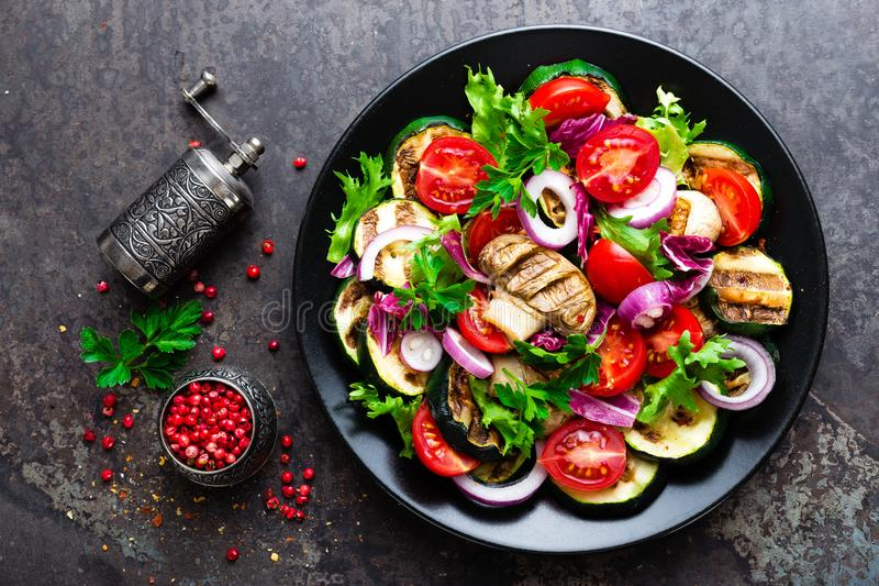 Salad with fresh and grilled vegetables and mushrooms. Vegetable salad with grilled champignons. Vegetable salad on plate stock photography