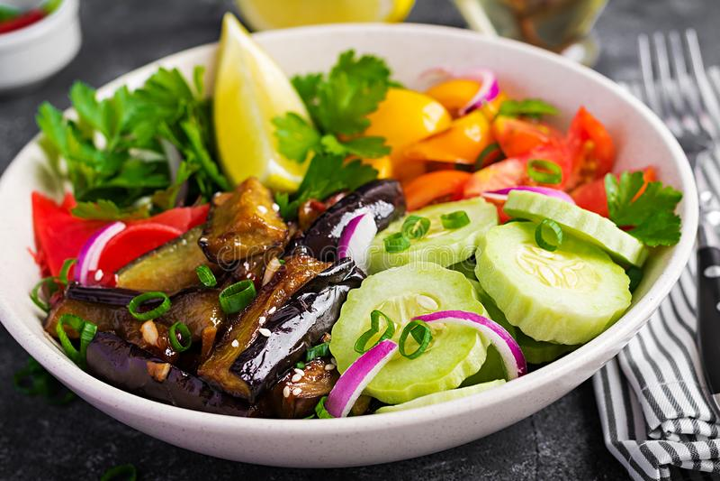 Salad fresh raw vegetables - armenian cucumber, tomatoes, paprika, parsley, red onion. And stewed eggplant. Vegan buddha bowl royalty free stock photos