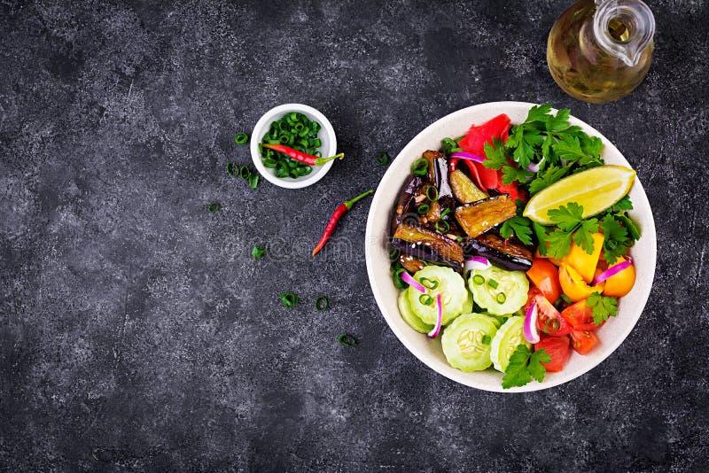 Salad fresh raw vegetables - armenian cucumber, tomatoes, paprika, parsley, red onion. And stewed eggplant. Vegan buddha bowl. Top view royalty free stock photo