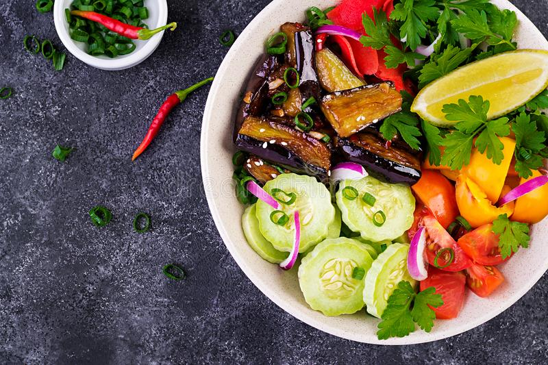 Salad fresh raw vegetables - armenian cucumber, tomatoes, paprika, parsley, red onion. And stewed eggplant. Vegan buddha bowl. Top view royalty free stock photography