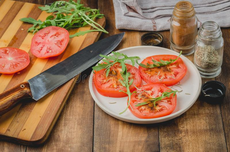 Salad. It is fresh the sliced tomatoes with arugula and seasonings in a white bowl. On a wooden background. Selective focus stock photo