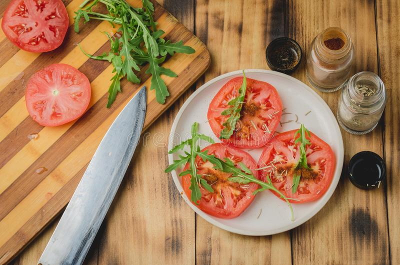 Salad. It is fresh the sliced tomatoes with arugula and seasonings in a white bowl. On a wooden background. Top view stock images