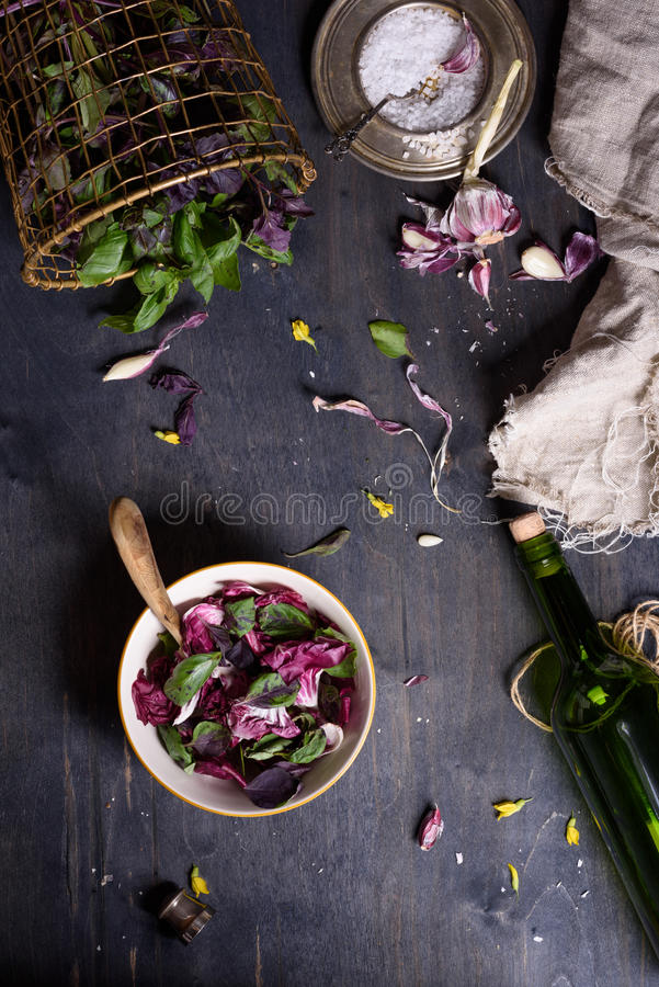 Salad with fresh summer greens and herbs on rustic wooden table. View from above, free text space. royalty free stock photo