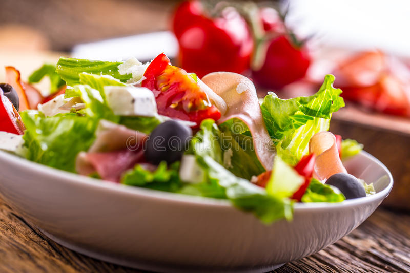 Salad. Fresh summer lettuce salad.Healthy mediterranean salad olives tomatoes parmesan cheese and prosciutto royalty free stock images