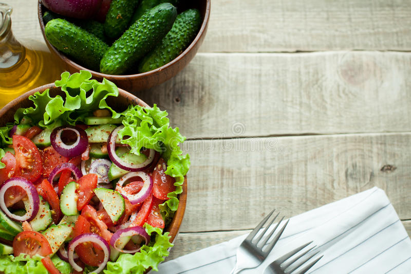 Salad of fresh tomatoes, cucumbers, red onions and lettuce, dressed with olive oil and ground pepper in a wooden bowl. Top view. Rustic salad of fresh tomatoes stock image