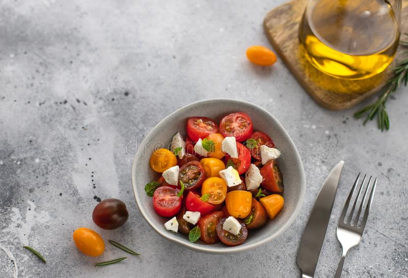 Salad with fresh tomatoes, feta cheese, basil, olive oil. Healthy snack concept stock image