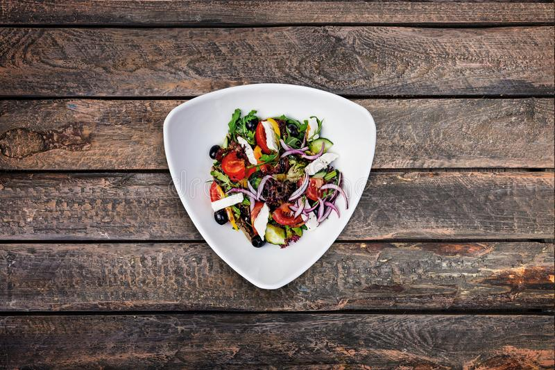 Salad of fresh vegetables with marinated goat cheese in Provencal herbs. stock photos