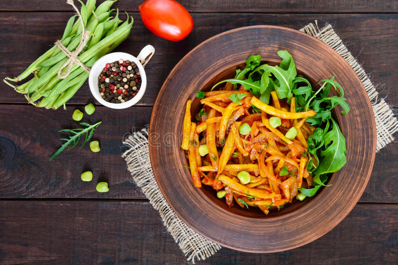 Salad from green beans, stewed with onions in tomato sauce and green leaves of arugula royalty free stock photo