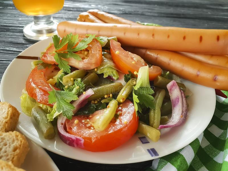Salad green beans, tomato, fried beef sausages snack traditional appetizer beer on a wooden background barbecue plate stock images