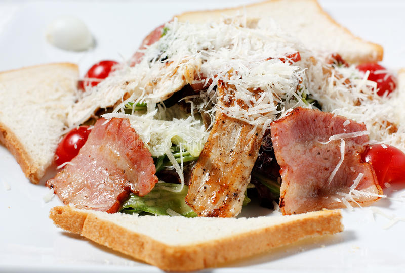 Salad greens with bacon, parmesan cheese, bread stock photo