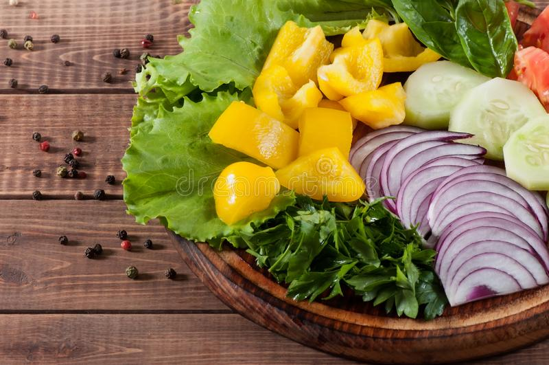 Salad of greens, tomatoes, cucumbers, sweet pepper onions on a wooden background stock images