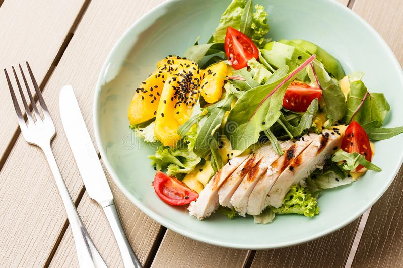 Salad with grilled chicken, mango, lettuce, avocado, tomatoes, arugula, cheese sause on a white plate on wooden stock photography