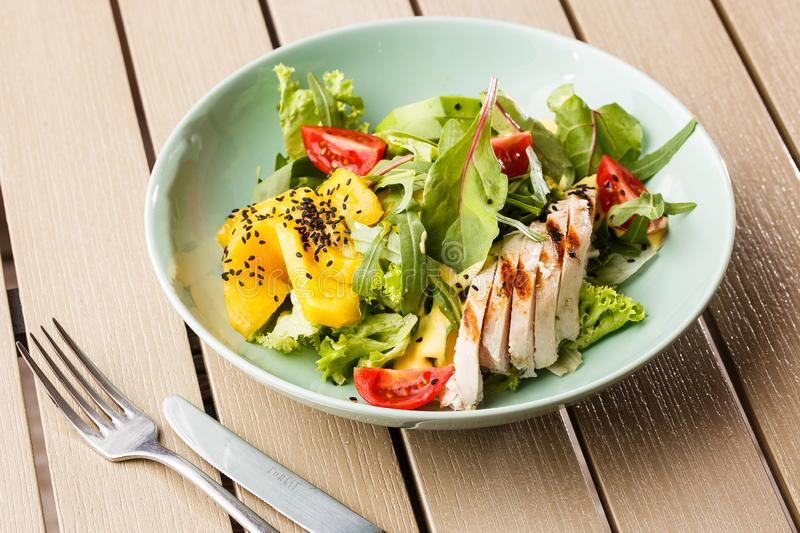 Salad with grilled chicken, mango, lettuce, avocado, tomatoes, arugula, cheese sause on a white plate on wooden royalty free stock photo