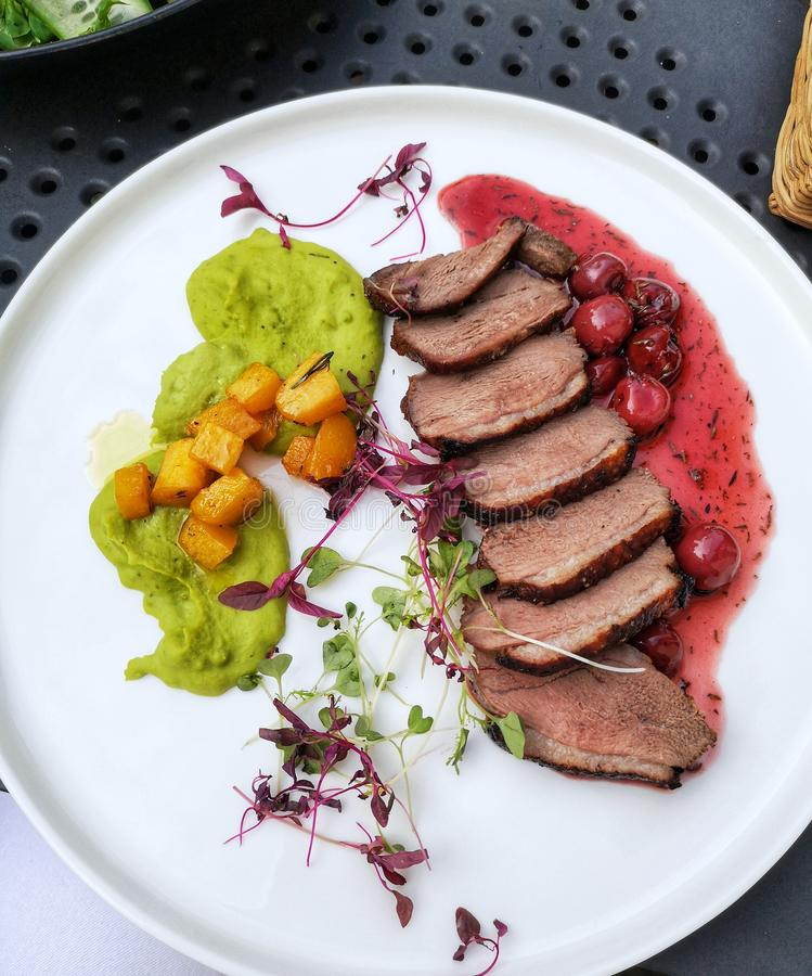 Salad of grilled goose, duck. Salad of grilled goose with cherries, peach, sprouts and parsley mousse on a white plate royalty free stock photography