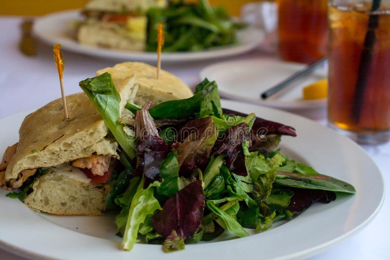 Salad and grilled Salmon sandwich in ciabatta bread in a restau royalty free stock photo