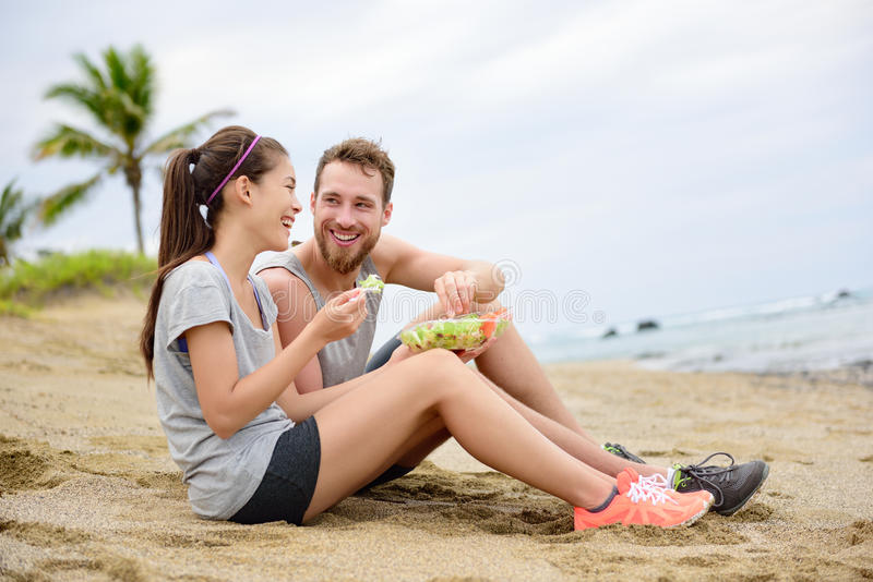Salad - healthy fitness couple eating food. Salad - healthy fitness women and men couple laughing eating food lunch sitting on beach after workout. Mixed race stock image