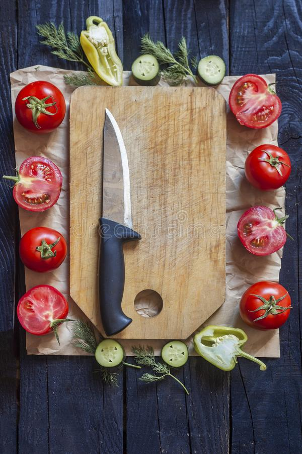 Salad ingredients. Fresh raw vegetables on wood. Healthy cooking salad. Cutting board with a kitchen knife royalty free stock photo