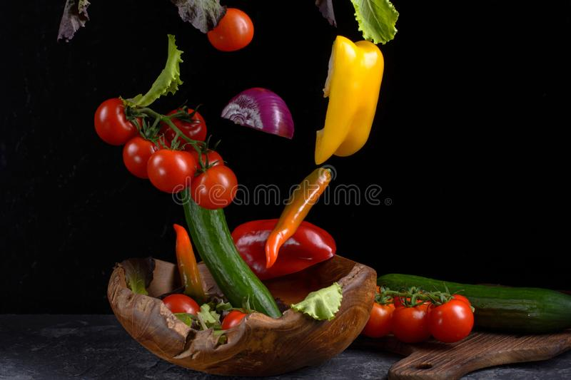 Salad ingredients levitation. Healthy vegetarian food is flying over a wooden bowl on a dark stone table with a cutting board and royalty free stock photo