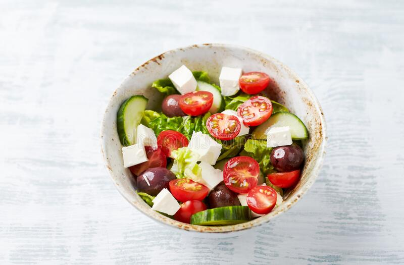 Salad with Kalamata Olives, Cucumber Cherry Tomatoes and Feta Cheese on bright wooden Background. Healthy Snack Idea. Close up royalty free stock photography