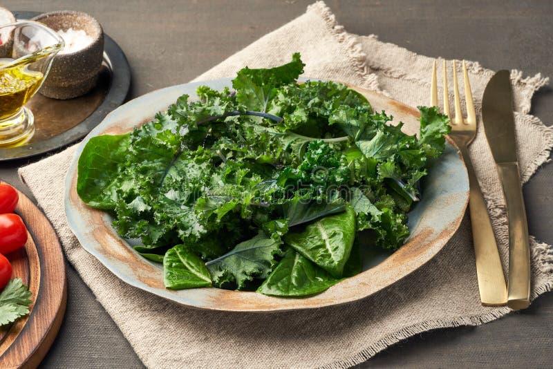 Salad kale, leaf cabbage, cos lettuce green mixture in plate. Undressed fresh leaves. Vegan. Salad kale, leaf cabbage and Romaine or cos lettuce green mixture in stock image