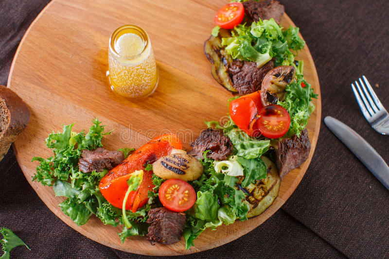 Salad leaves with sliced roast beef and sun-dried cherry tomatoes stock image