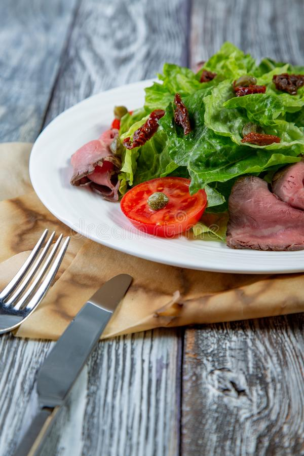 Salad leaves with sliced roast beef and sun-dried cherry tomatoes on wooden background royalty free stock photos