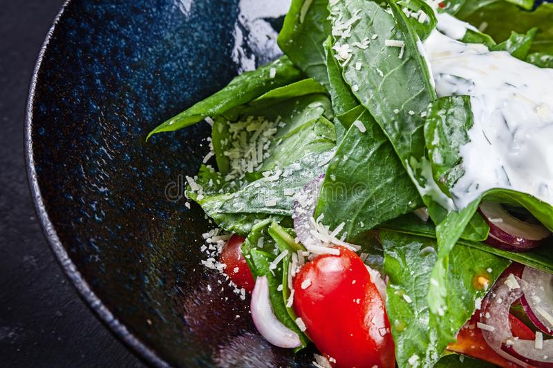 Salad with lettuce, sour cream sauce, cherry tomatoes, red onion and parmesan. Copy space. Concept of healthy food. Lunch or tasty royalty free stock images