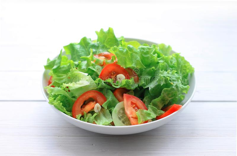 Salad of lettuce, tomatoes and cucumbers in a plate on a light wooden background royalty free stock photo