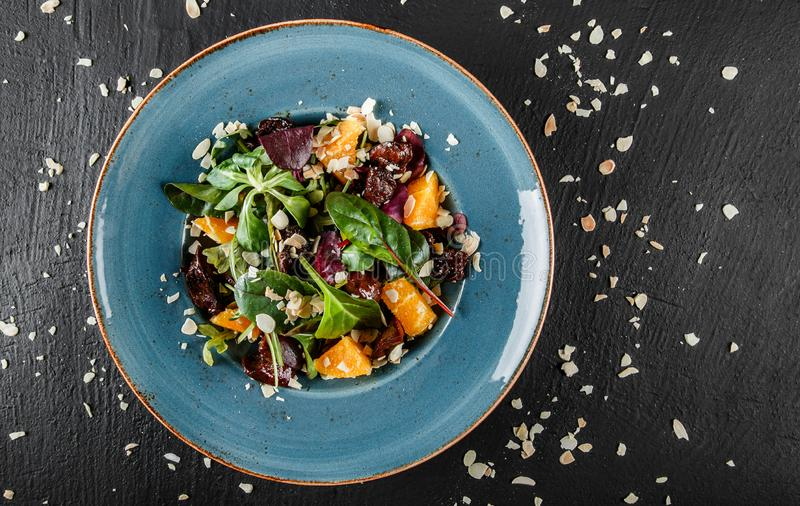 Salad with liver, arugula, orange, spinach and almonds on plate over dark stone surface. Healthy food concept. Top view stock image